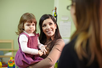 Woman Holding Toddler While Talking to Another Woman