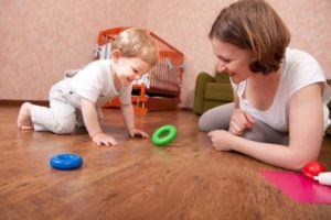 Woman and Toddler Playing with Large Rings on Floor