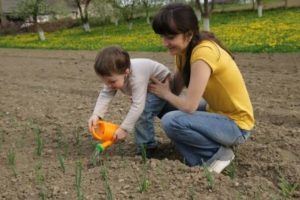Adult and Toddler Watering a Garden