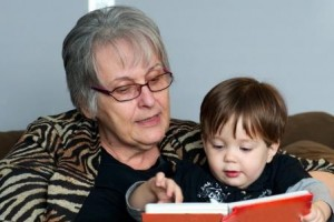 Elderly Person Reading Book to Toddler