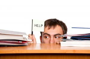 Man holds up a help sign while looking between stacks of papers.