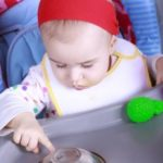 Baby plays with toys on high chair tray