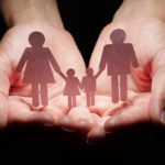 Hands holding a paper cut out family.