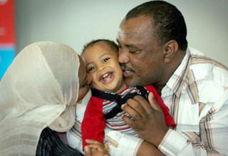 African American parents kiss their baby that is between them.