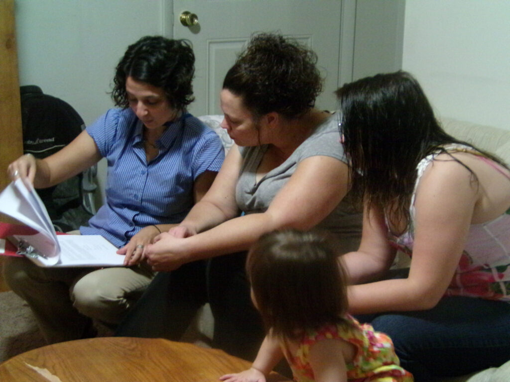 Early interventionist explaining COS process to mother in family's home.